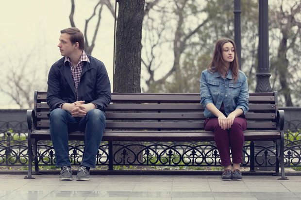 boy and girl sitting apart on bench