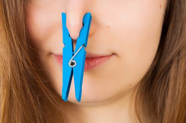 Girl with a blue clothes peg on her nose.