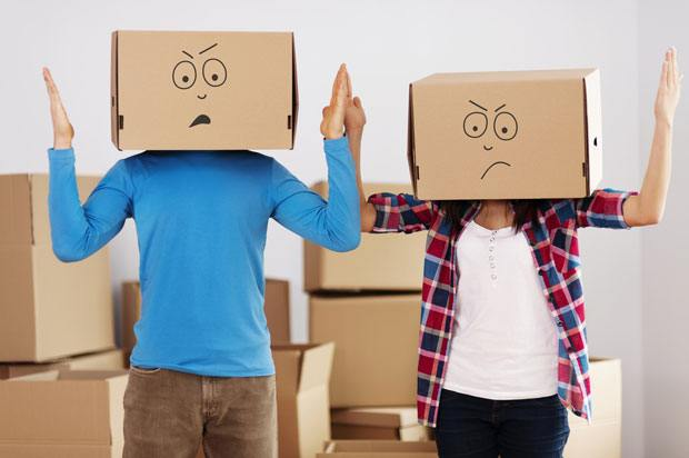 Couple with moving boxes on their heads