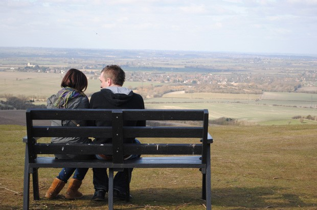 girl and boy sat on a bench in the countryside
