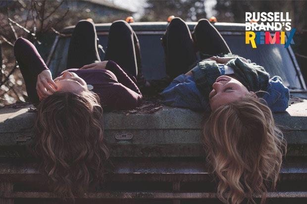 two teenage girls lying on a car bonnet