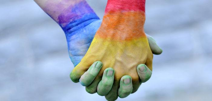 two hands intertwined covered in gay pride coloured paint
