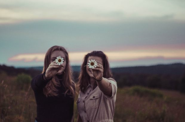 Two friends hug each other and hold out flowers