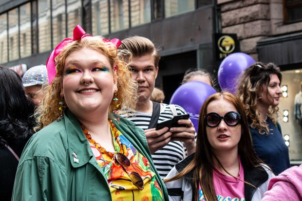 A group of young people celebrating outside. In the forefront is a young woman smiling with colourful eyeshadow, stood by her a young woman with sunglasses on.
