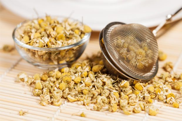 Picture of chamomile buds some in a tea strainer