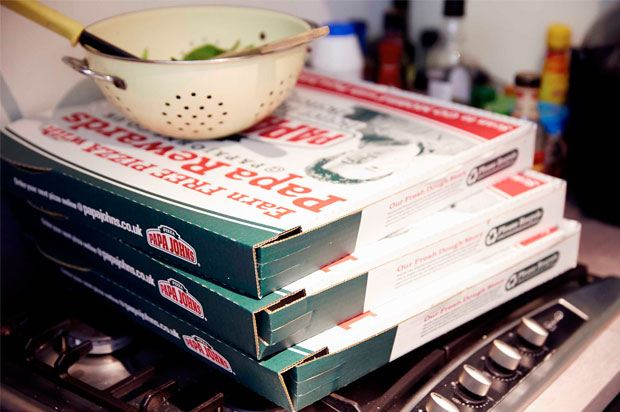 Pile of pizza boxes with colander on top