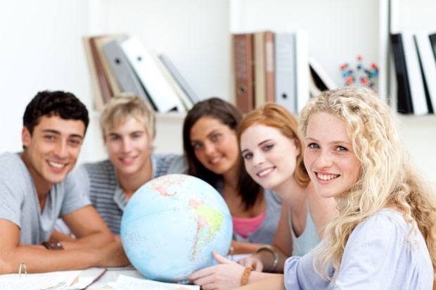 Students smiling all sat around a globe