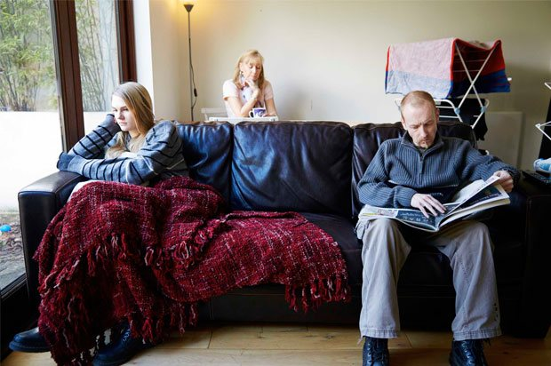 Girl sat on other side of sofa from dad and mum sat behind