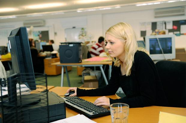 Girl sat in office at a computer