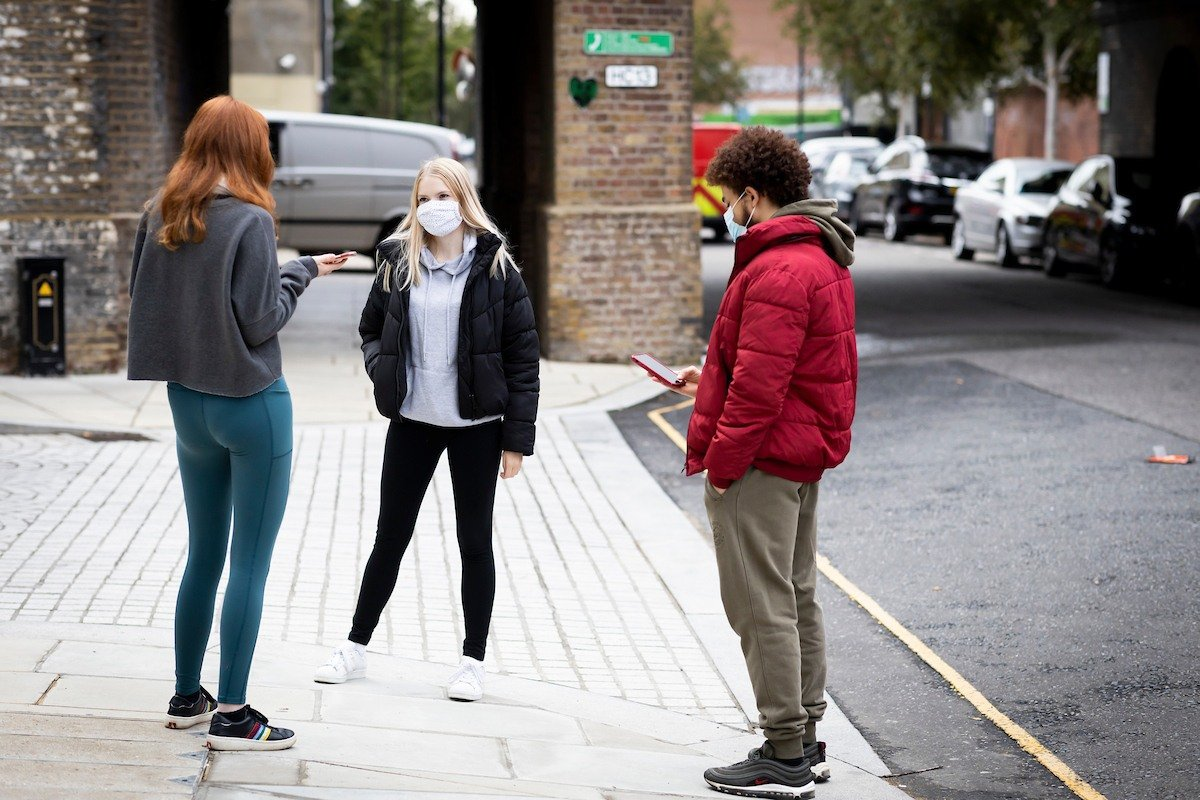 A group of young people are standing on a pavement. They are thinking about being a social smoker. This is a full-body image.