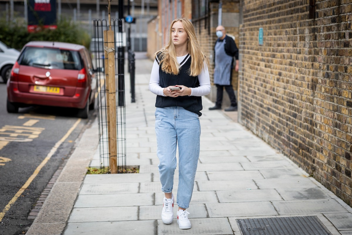 A blonde young-woman is walking down the street. She is wearing a black vest over a white polo and light blue jeans. She is looking into the distance, recalling getting hit by a drunk driver. This is a wide-angle image.