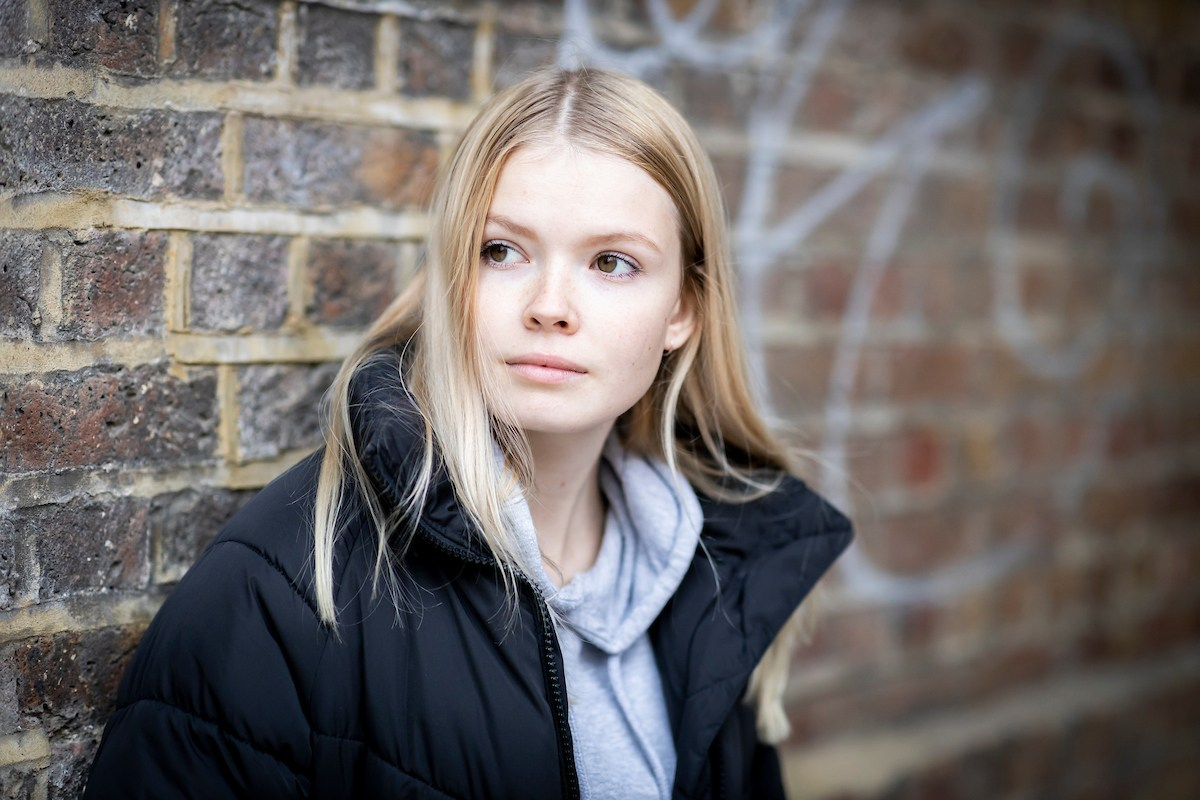 A young,blonde woman is leaning on a brick wall. She is looking to the side, worried. She is thinking about when she was on drugs at 13. This is a close-up image.