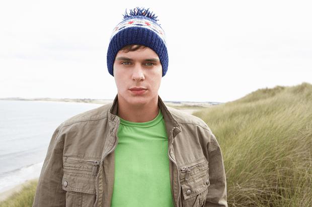 Teenage boy standing in sand