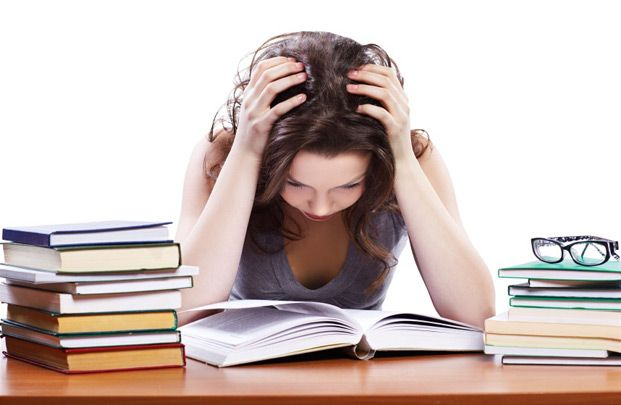 girl with head in hands looking stressed over books