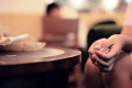 Image of the hands of a girl sitting by a table