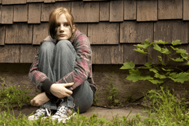 Young girl sits on the ground with her back to a wall looking afraid