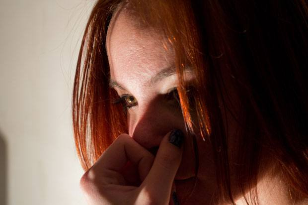 A girl with red hair looks into the distance. Half of her face is in shadows.