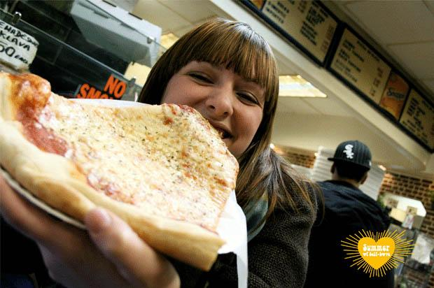 girl eating big slice of pizza