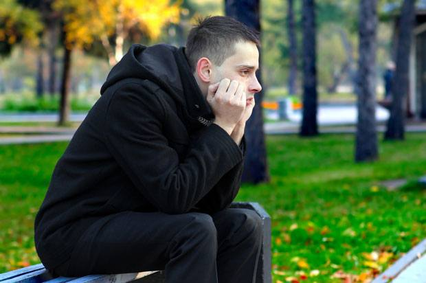 young man sits on bench in park looking upset.