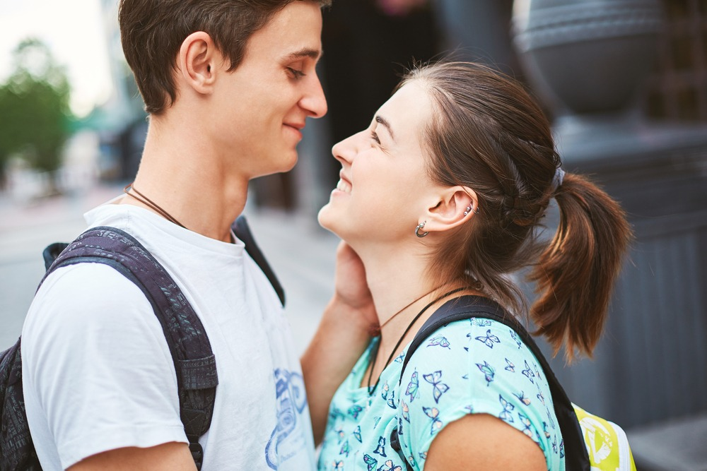 A young couple is staring at each other lovingly. They are discussing drunk sex. This is a close-up image.