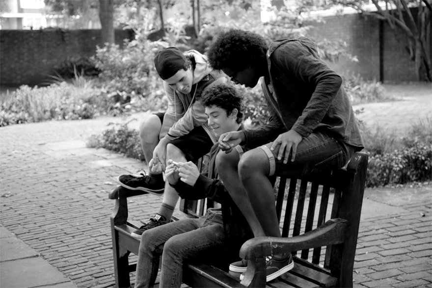 Group of young men looking at a mobile phone