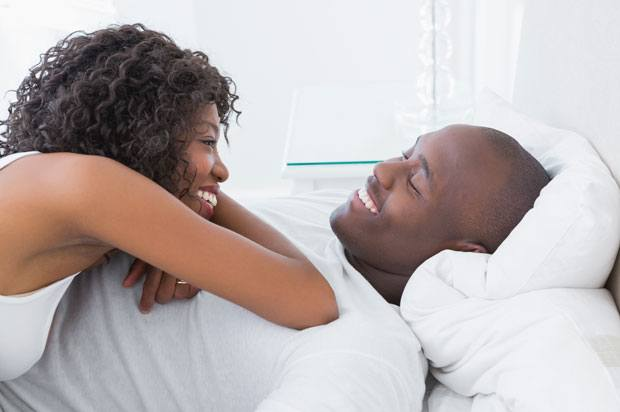 A man lies on his back on bed whilst a woman lies on top of him. They are both smiling.