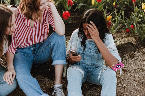 Three friends sitting down in a field looking at their mobiles and speaking to one another