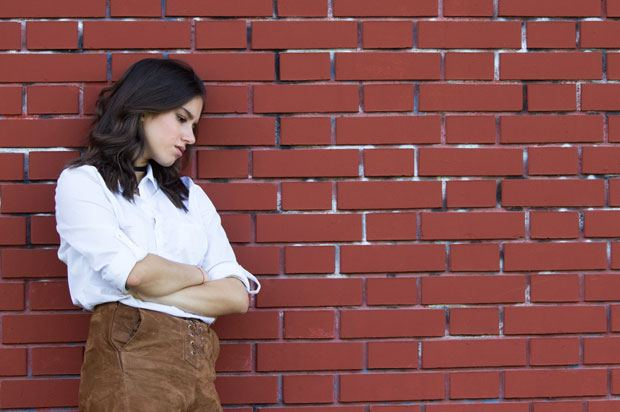 woman stand against a brick wall looking upset.
