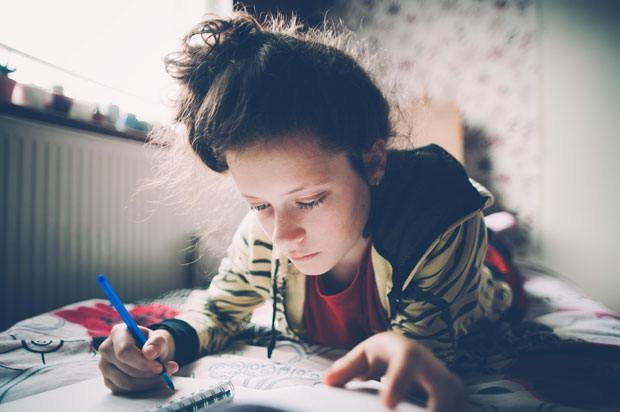 girl revising on bed