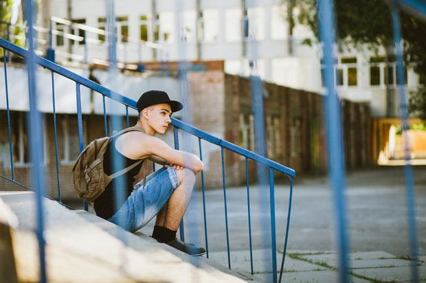 person sits on steps outside a large building. There are railings in front of the camera.