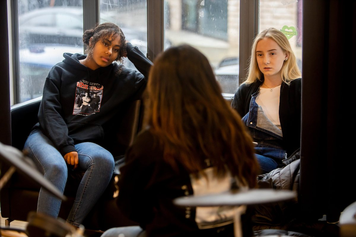 Three young women are sitting on couches. Two young women are facing the camera, listening to their friend. She is recalling her boyfriend taking pain relief on cocaine. This is a wide-angle image.