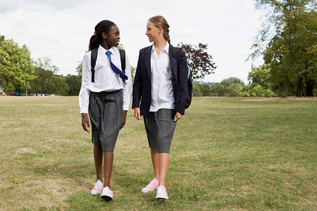 Two school girls walk across an open field talking to each other.