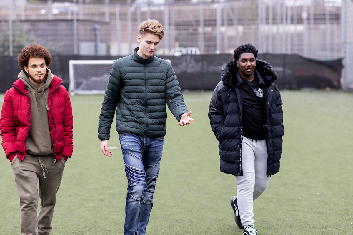 Three young men are walking on a field. They are all wearing puffer jackets. They are discussing the link between toxic masculinity and binge drinking. This is a wide angle image.