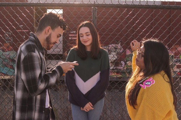 Three friends hanging out together . Far left a boy witha checkered shirt on his phone, middle girl leaning on a metal fence, left a girl in a yellow jumper with one hand on fence.
