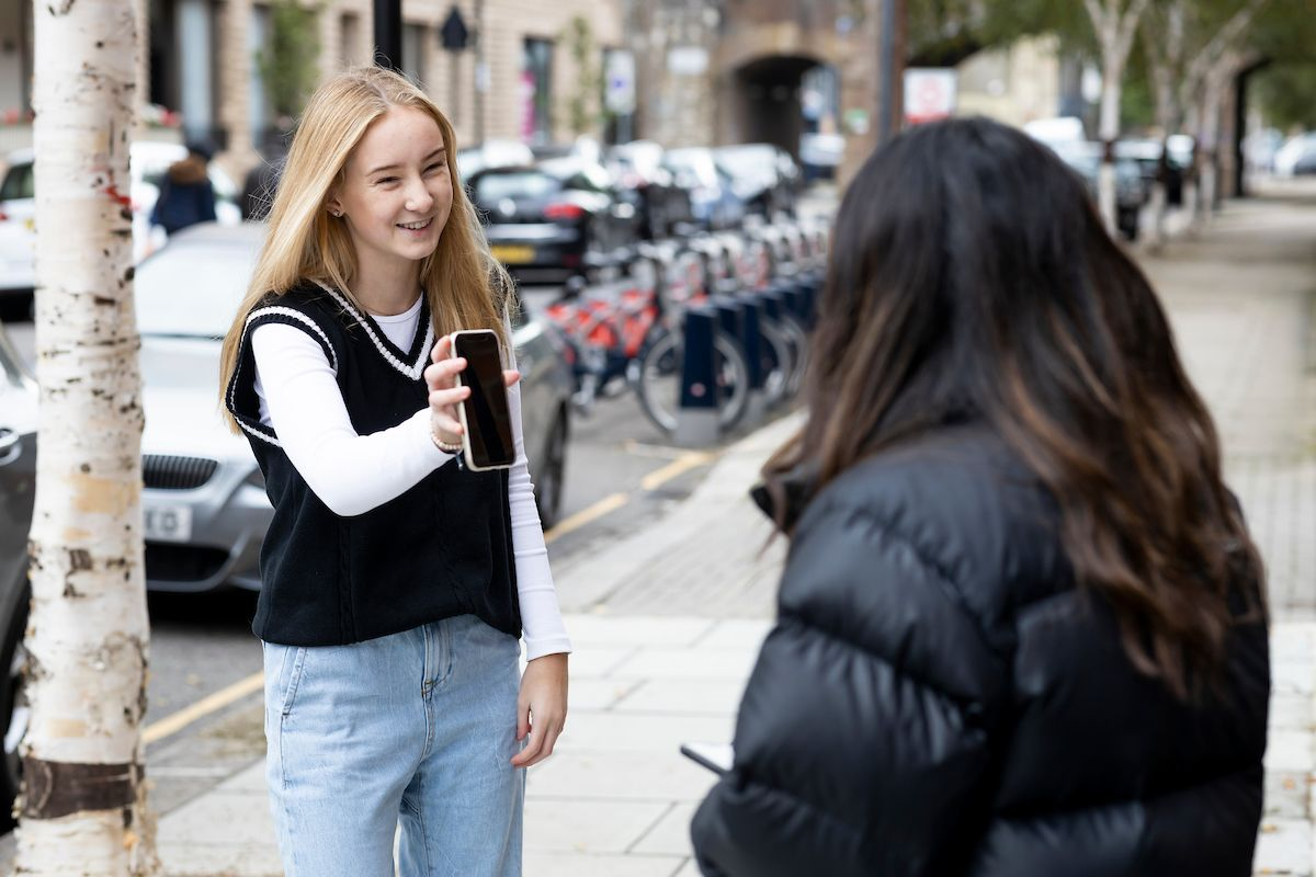 Two young women are standing on the pavement. One friend is showing the other DIY drug kits on the phone. This is a wide-angle image.