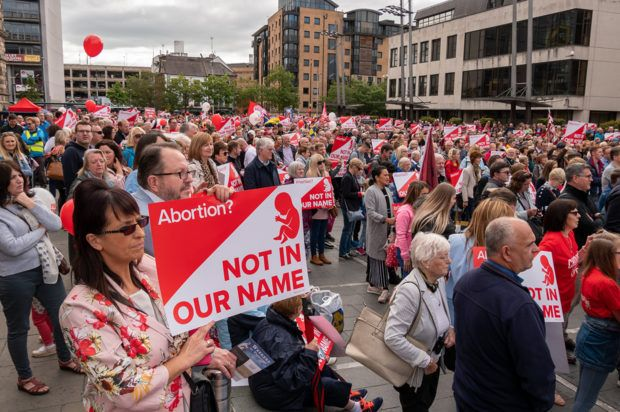 A group of protesters hold up anti-abortion signs
