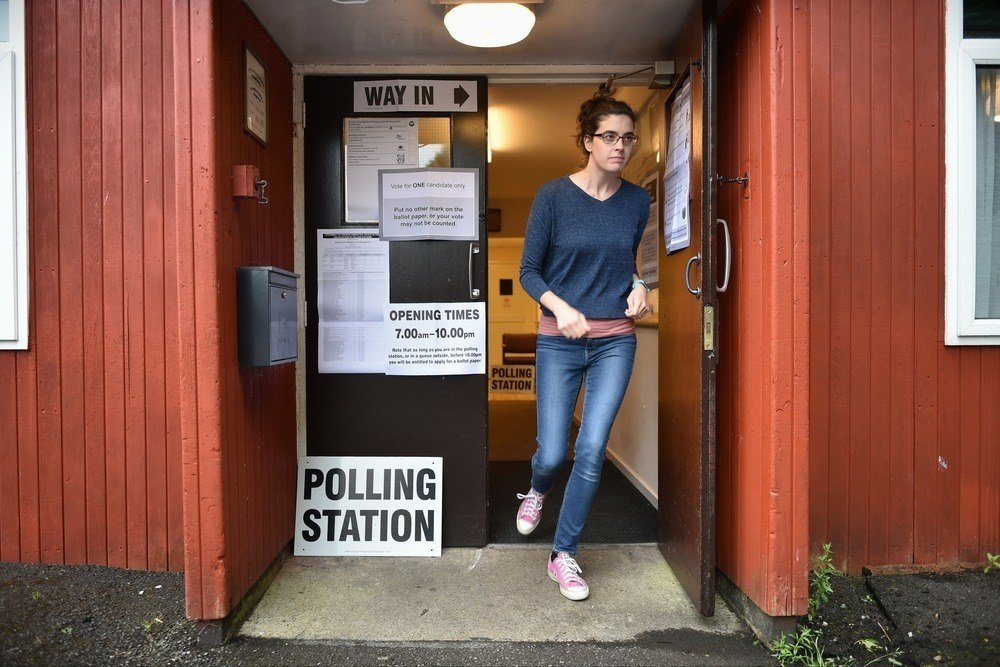 A young woman leaves a polling station