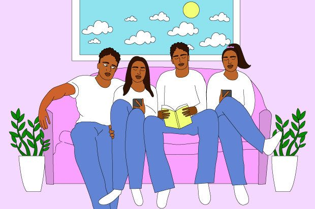 A family are sitting together, sharing a space on a pink sofa in their home