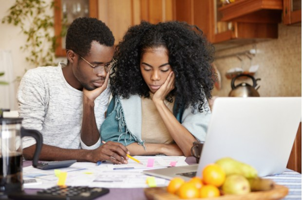 two young people sit at a laptop looking like they're concentrating.