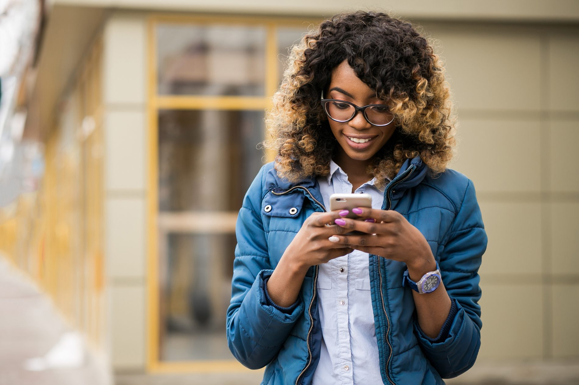 A young person smiles while using their phone