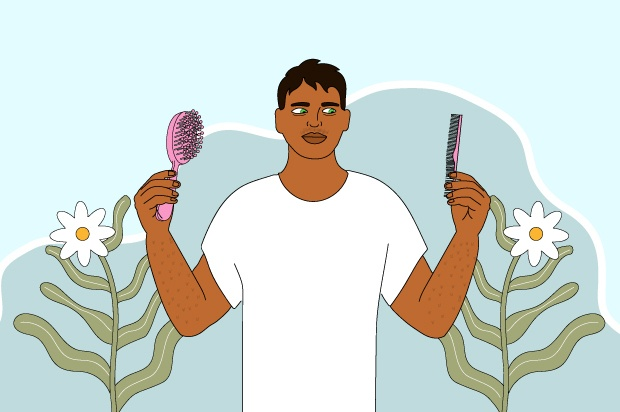 A young person is holding a purple brush and a comb. There are flowers around him.