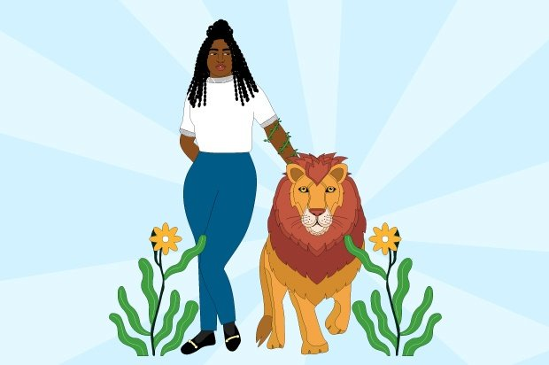 A young person stands confidently next to a lion with her hand on its back.