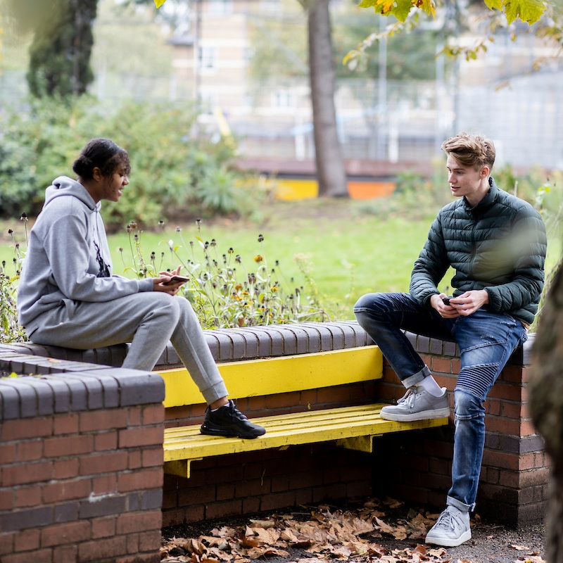 Two young people are talking on a bench