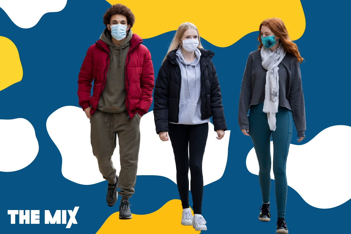 Three young people are walking side by side wearing masks