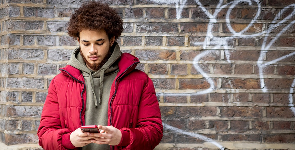 A young person is on their phone standing outside
